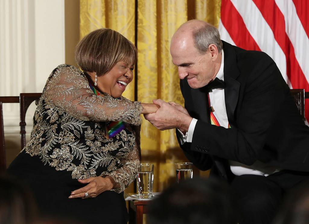 . Recipient of the 2016 Kennedy Center Honors, gospel and blues singer Mavis Staples, left, gives musician James Taylor, a fist bump during a reception in their honor in the East Room of the White House in Washington, Sunday, Dec. 4, 2016, hosted by President Barack Obama and first lady Michelle Obama. (AP Photo/Manuel Balce Ceneta)