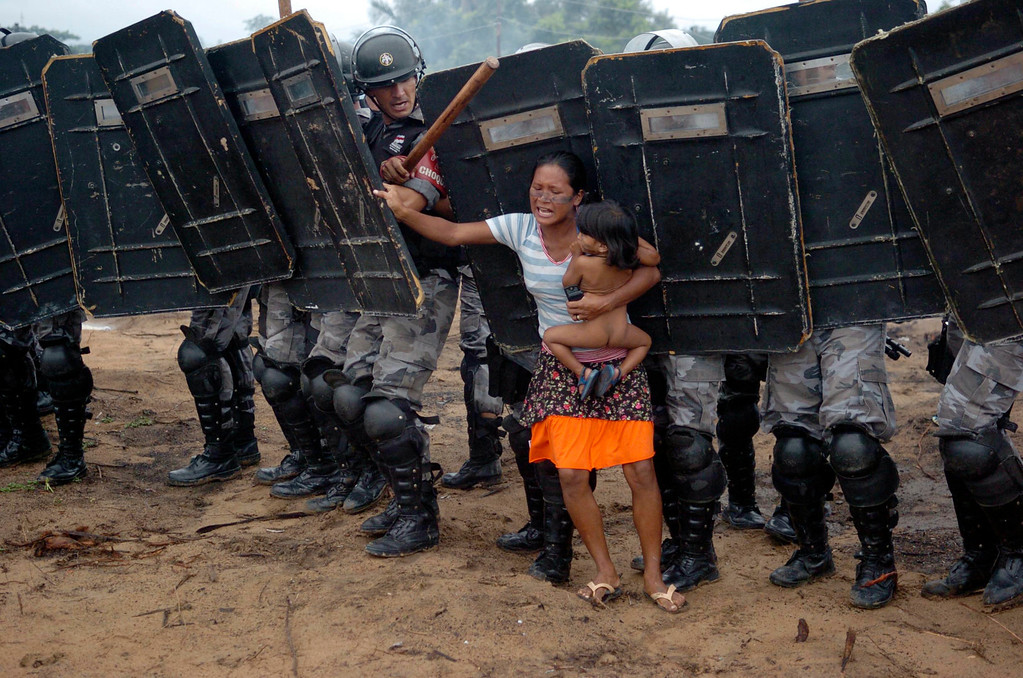 . An indigenous woman holds her child while trying to resist the advance of Amazonas state policemen who were expelling the woman and some 200 other members of the Landless Movement from a privately-owned tract of land on the outskirts of Manaus, in the heart of the Brazilian Amazon March 11, 2008. The landless peasants tried in vain to resist the eviction with bows and arrows against police using tear gas and trained dogs. REUTERS/Luiz Vasconcelos-A Critica/AE