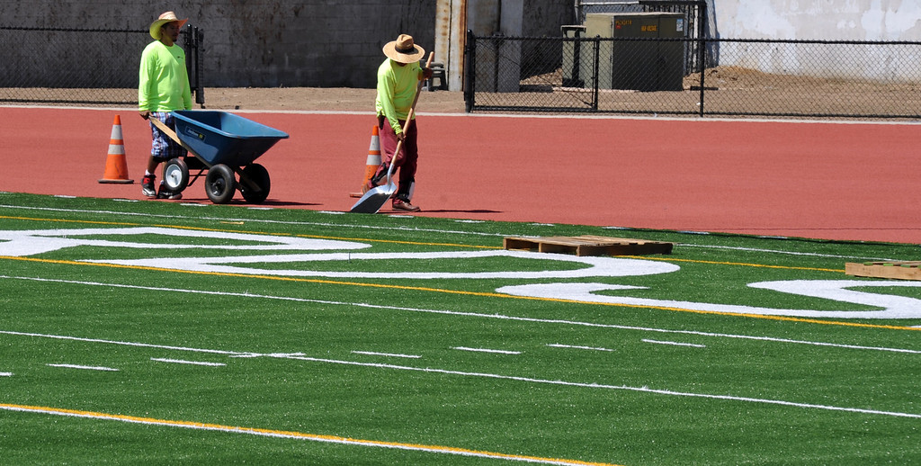 . Workers finish up the newly completed Astroturf football field at St. Paul High School in Santa Fe Springs on Friday August 9, 2013. St. Paul officials, students, and alumnae will dedicate the school\'s new football field and volleyball and basketball floors on Saturday.