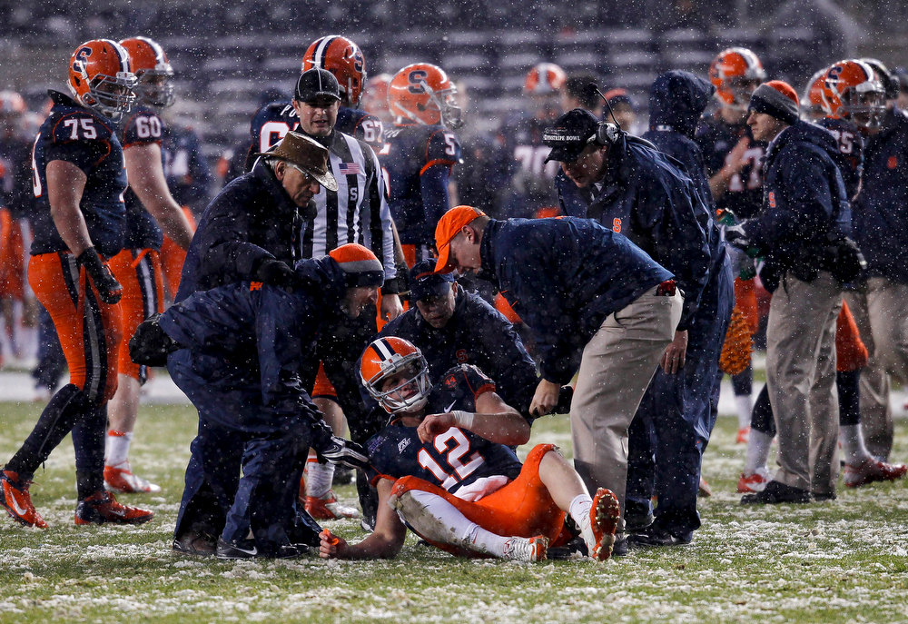 . Ryan Nassib #12 of the Syracuse Orange is helped back to his feet after being sacked by the West Virginia Mountaineers in the New Era Pinstripe Bowl at Yankee Stadium on December 29, 2012 in the Bronx borough of New York City.  (Photo by Jeff Zelevansky/Getty Images)