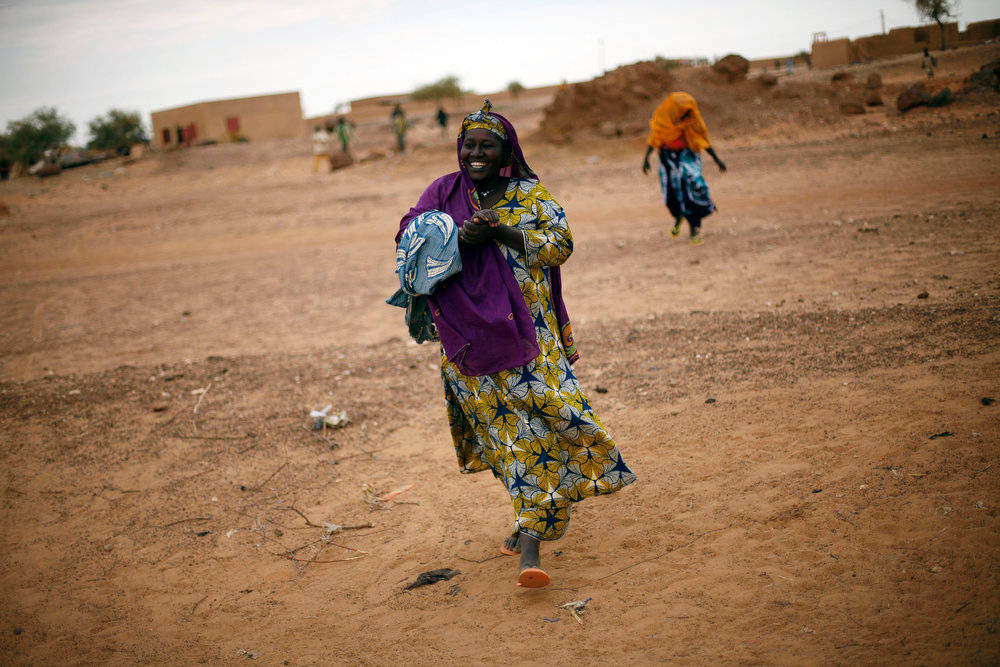 . A Malian woman runs smiling towards a car loaded with travelers in Gossi, some 150 km from  Gao, Northern Mali, Monday Jan. 28, 2013. French and Malian troops held a strategic bridge and the airport in the northern town of Gao on Sunday as their force also pressed toward Timbuktu, another stronghold of Islamic extremists in northern Mali, officials said. (AP Photo/Jerome Delay)