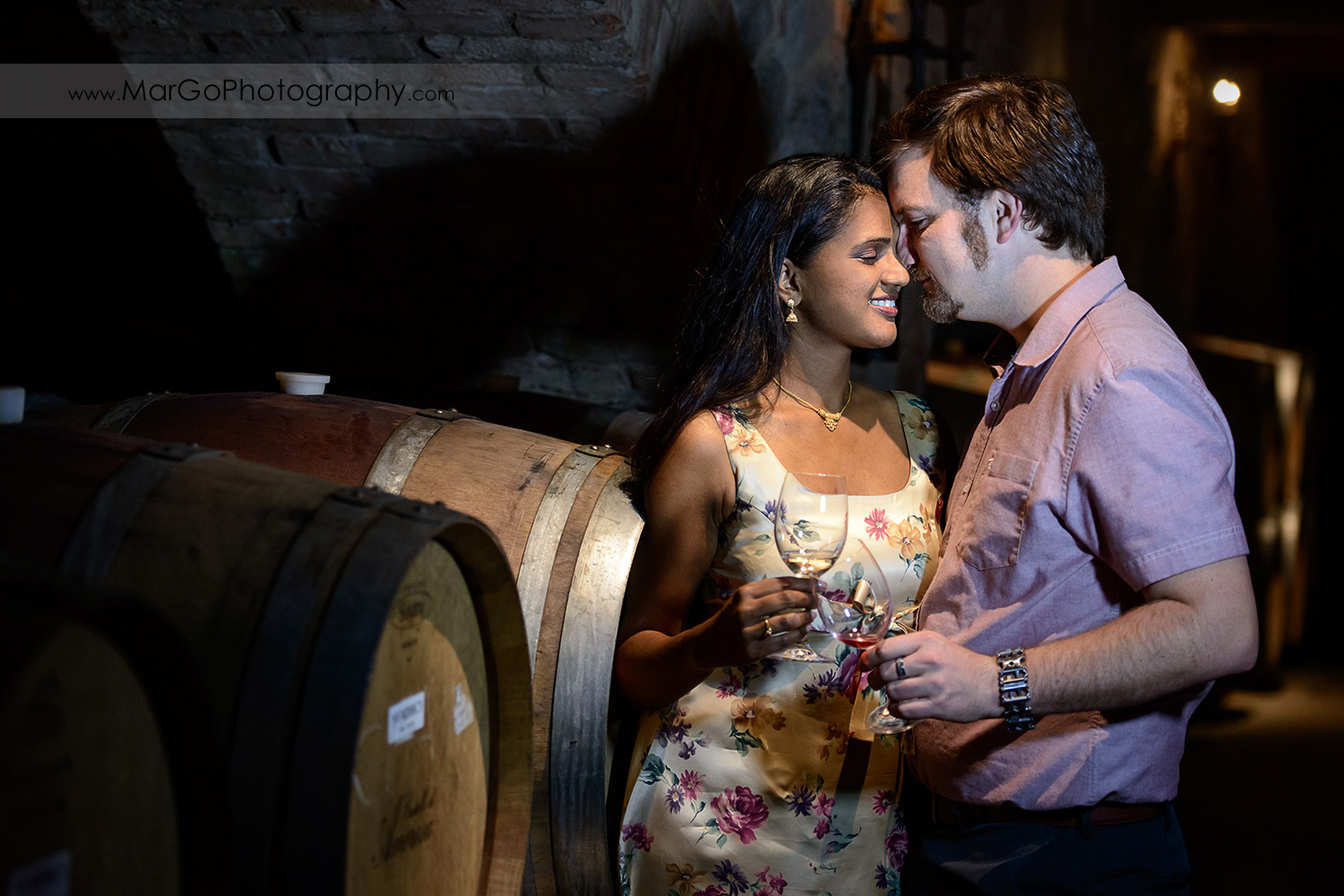 man in pink shirt and Indian woman in flower dress holding wine glasses in the wine cellar during engagement session at Castello di Amorosa in Calistoga