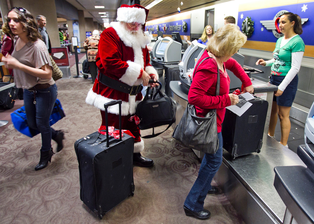 . In this Wednesday, 21, 2011, file photo, holiday travelers, including Donald Occimio of Mesa, Ariz., dressed as Santa Claus, and his wife Diane check in with customer service agent Angelee Arciniega, right, for their Southwest Airlines flight at the Terminal 4 ticketing area at Sky Harbor International Airport, in Phoenix. The 2012 Christmas travel season could be the busiest in six years, with AAA predicting that 93.3 million Americans will hit the road. That\'s 1.6 percent more than last year and just 400,000 people shy of the 2006 record.  (AP Photo/The Arizona Republic, Tom Tingle)