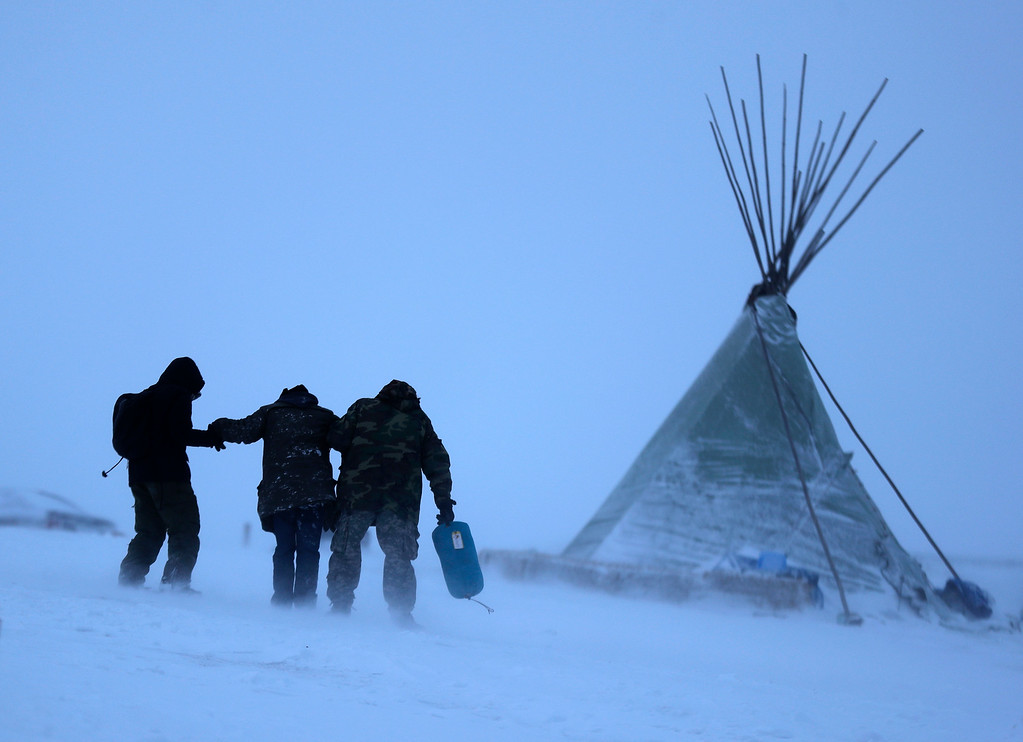 . People walk along a snowy hillside in a storm at the Oceti Sakowin camp where people have gathered to protest the Dakota Access oil pipeline in Cannon Ball, N.D., Monday, Dec. 5, 2016. Many Dakota Access oil pipeline opponents who\'ve gathered for months in the camp in southern North Dakota are committed to staying despite wintry weather and demands that they leave. (AP Photo/David Goldman)