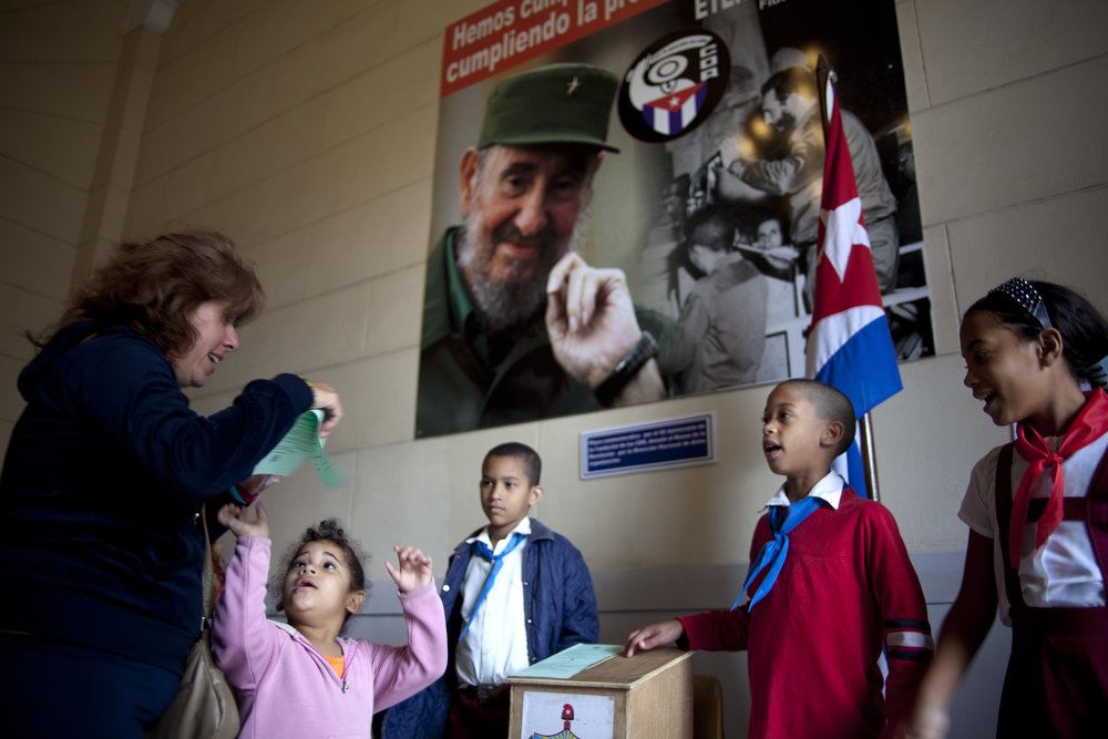 Description of . Under a picture of Cuba's leader Fidel Castro, Cuban schoolchildren check a voter is properly casting his ballot at a polling station during parliament elections in Havana, Cuba, Sunday, Feb. 3, 2013. More than 8 million islanders are eligible to vote and will approve 612 members of the National Assembly and over 1,600 provincial delegates. (AP Photo/Ramon Espinosa)