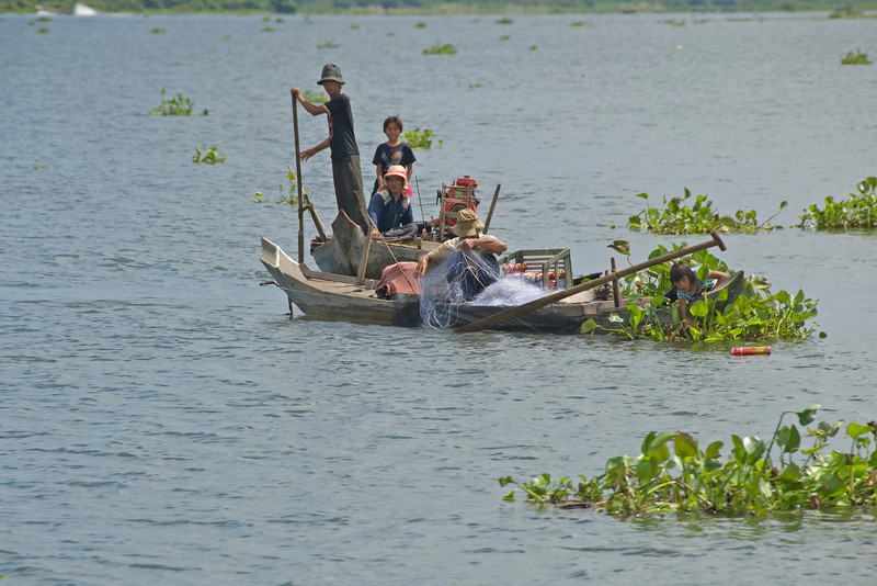 A fishing family throwing a fishing net on the Tonle Sap river
