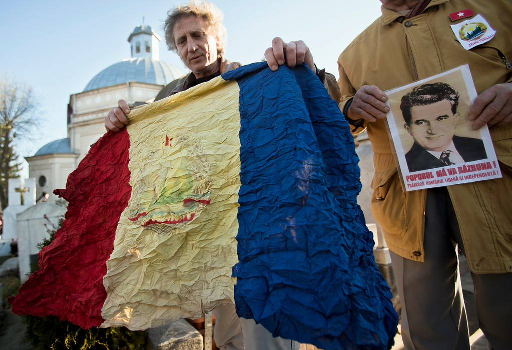 . Men hold a picture of Romanian communist dictator Nicolae Ceausescu and a communist era Romanian national flag they call \'a treasure\' as communism nostalgics gather around his grave in Bucharest, Romania,  Thursday, Dec. 25, 2014, 25 years after he and his wife Elena were executed by firing squad on Christmas day 1989. Romanians, especially those of a more senior age, have mixed feelings about the former dictator and his rule, 25 years after his execution, with many remembering predominantly the positive aspects, like the social security, of the communist times and not focusing on the extreme economic hardships and lack of basic human rights of that period.  (AP Photo/Vadim Ghirda)