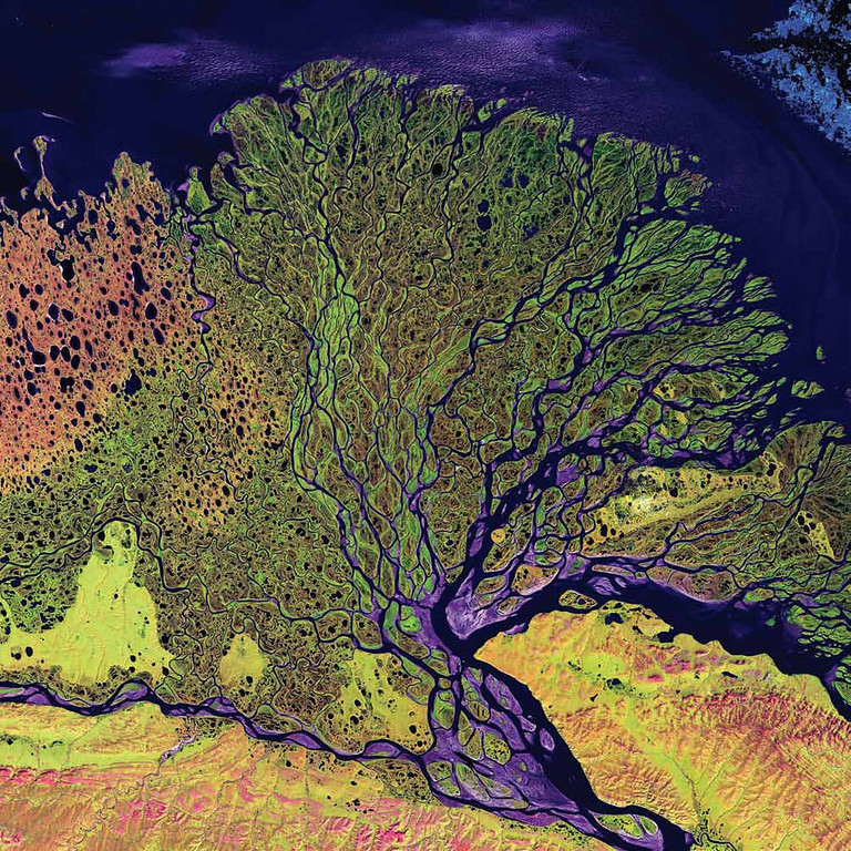 . Lena River Delta, Russia The Lena River Delta in Siberia extends 100 kilometers into the Laptev Sea and Arctic Ocean, and it includes an extensive protected wilderness area and wildlife refuge. In this Landsat 7 image from 2000, vegetation appears as shades of green, sandy areas as shades of red, and water as purples and blues. The Lena River Delta is about 400 kilometers wide, and it divides into a multitude of flat islands. The delta is frozen tundra for about 7 months of the year, and spring transforms the region into a lush wetland.   NASA