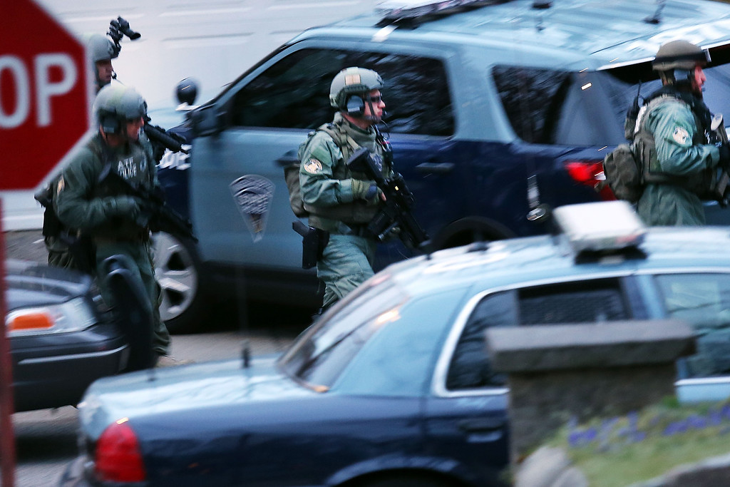 . WATERTOWN, MA - APRIL 19:  Members of a police S.W.A.T. team run to the scene where it was believed 19-year-old bombing suspect Dzhokhar A. Tsarnaev  is in hiding on April 19, 2013 in Watertown, Massachusetts. After a car chase and shoot out with police, one suspect in the Boston Marathon bombing, Tamerlan Tsarnaev, 26, was shot and killed by police early morning April 19, and a manhunt is underway for his brother and second suspect, 19-year-old suspect Dzhokhar A. Tsarnaev. The two men, reportedly of Chechen origin, are suspects in the bombings at the Boston Marathon on April 15, that killed three people and wounded at least 170.  (Photo by Spencer Platt/Getty Images)