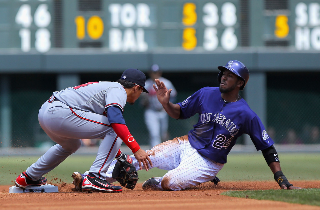 . Shortstop Ramiro Pena #14 of the Atlanta Braves tags out Dexter Fowler #24 of the Colorado Rockies to complete and double play and end the first inning at Coors Field on April 24, 2013 in Denver, Colorado.  (Photo by Doug Pensinger/Getty Images)