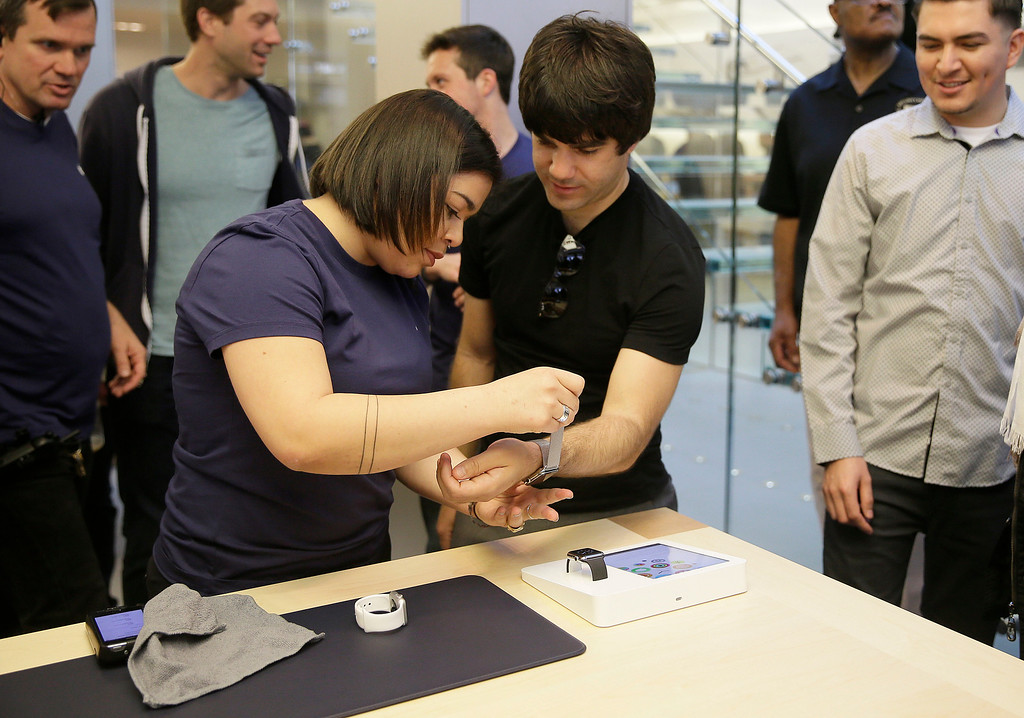 . An Apple store worker, left, helps a  customer try on Apple\'s new watch in San Francisco, Friday, April 10, 2015. Apple has started taking orders for the watch on its website and the Apple Store app. Currently, that\'s the only way Apple is selling the watch, with shipments scheduled to start April 24. (AP Photo/Eric Risberg)