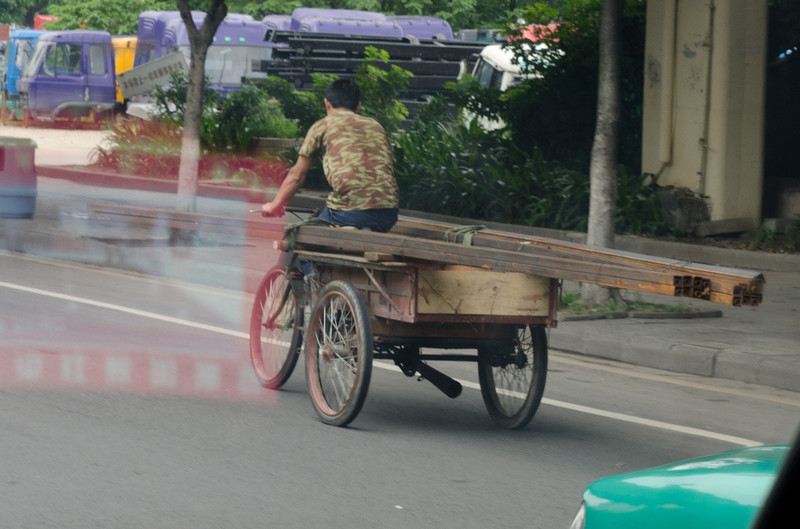The next 2 photos show a gyu hauling 20 foot sticks of steel - on a motorized trike through traffic.  Look at that load!!  NO idea how the tires handle it.  There are sticks of round pipe inside the square tube too!