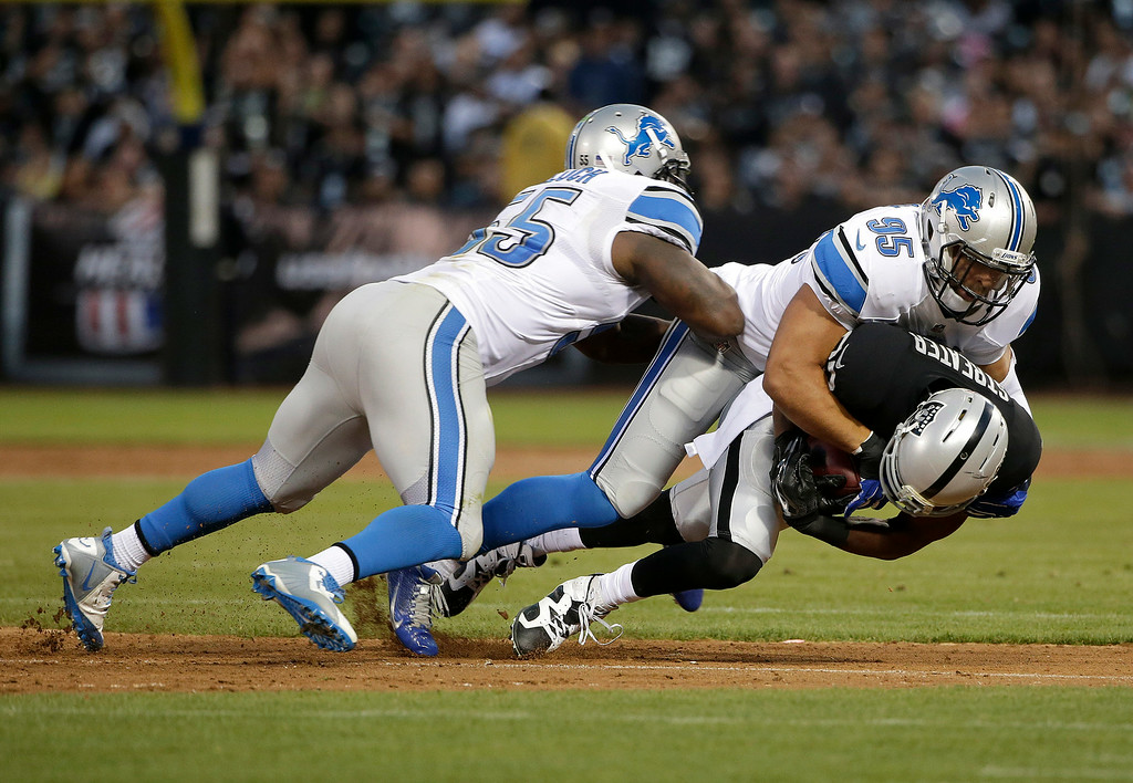 . Detroit Lions outside linebacker Kyle Van Noy (95) and middle linebacker Stephen Tulloch (55) tackle Oakland Raiders wide receiver Rod Streater (80) during the second quarter of an NFL preseason football game in Oakland, Calif., Friday, Aug. 15, 2014. (AP Photo/Marcio Jose Sanchez)