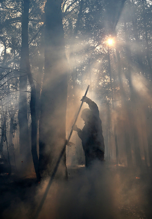 . Firefighters mop up after a firestorm swept through a property in Bilpin, 75 kilometers (47 miles) from Sydney, Wednesday, Oct. 23, 2013.  (AP Photo/Rob Griffith)
