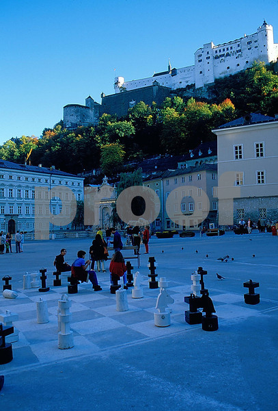 Chess players in Salzburg, Austria with the old ruins on the hill above.