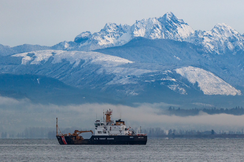 Coast guard ship in front of mountains and fog