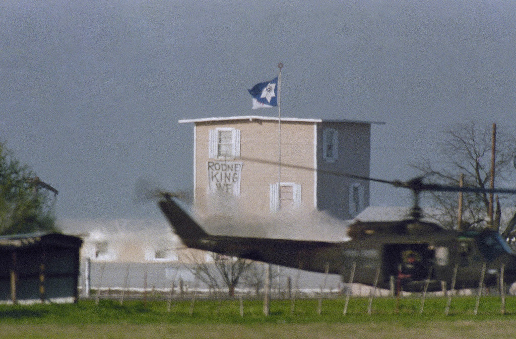 ". An Army helicopter flies low and near the Branch Davidian compound near Waco, Texas on Friday, April 3, 1993. The helicopter partially obscures a banner hung out a compound window by cult members reading ""Rodney King, we understand.\"" (AP Photo/Charles Krupa)"