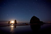 The moon sets between the Needles during a 7 minute exposure that shows the trails of the stars above Haystack Rock. In the northern hemisphere, the stars rotate counter clockwise, with the north star as the center.