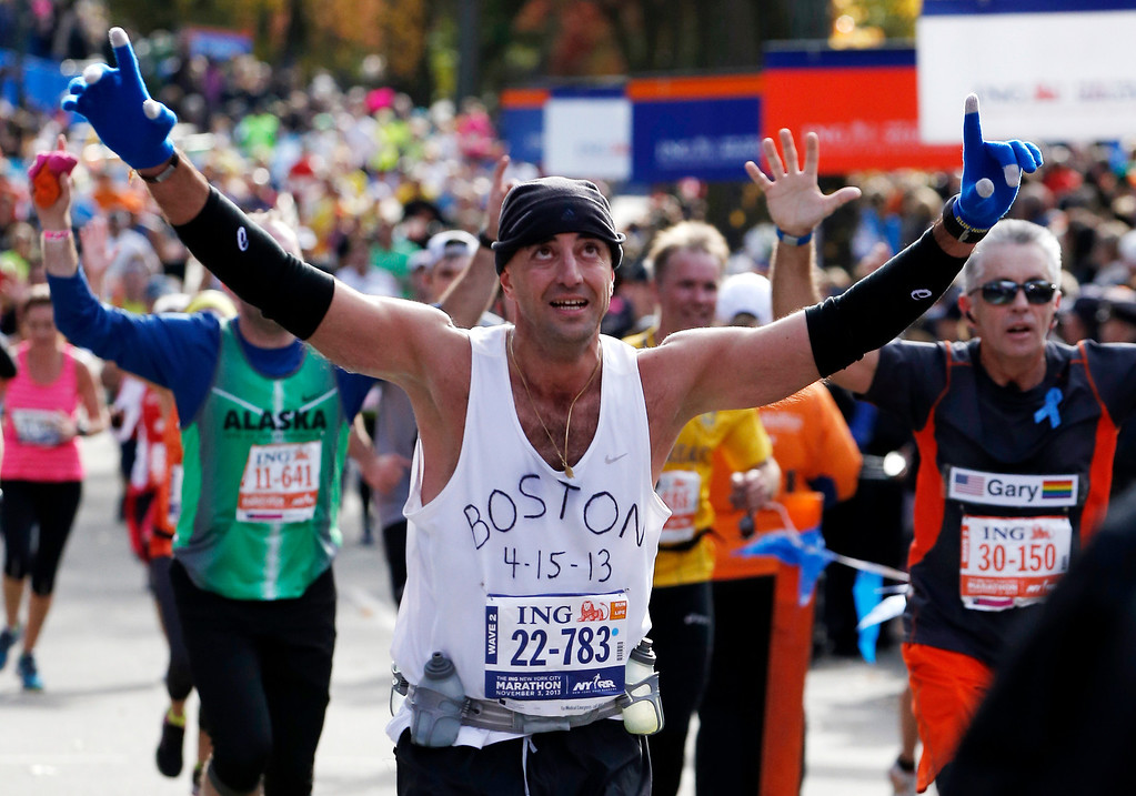 . Wearing a shirt that pays tribute to victims of the Boston Marathon bombings, Andrew Mangone of the United  States reacts crossing the finish line after completing the New York City Marathon, Sunday, Nov. 3, 2013, in New York. (AP Photo/Kathy Willens)