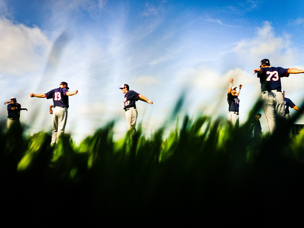 . Minnesota Twins players warm up while seen through the lush green grass of their well-kept practice fields. (Pioneer Press: Ben Garvin)