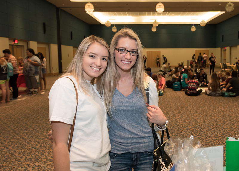 Hannah Fick and emily Suculla sign up for the raffle items at the PAWs on the Island event.