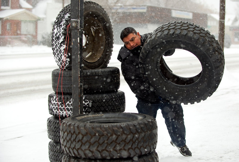 . The metro area got hit with snow on Wednesday, December 19, 2012.  Manuel Flores stacks snow tires for a display at Denver Tire on E. Colfax Ave in Denver. Cyrus McCrimmon, The Denver Post
