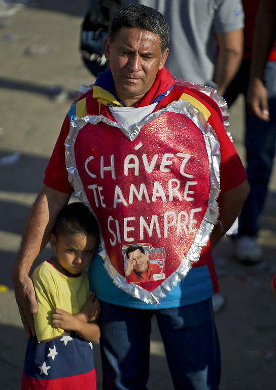 ". A supporter of the late President Hugo Chavez is seen outside of his funeral wearing a heart that reads ""Chavez, I will always love you\"" in Caracas, on March 8, 2013.  AFP PHOTO/Ronaldo  Schemidt/AFP/Getty Images"