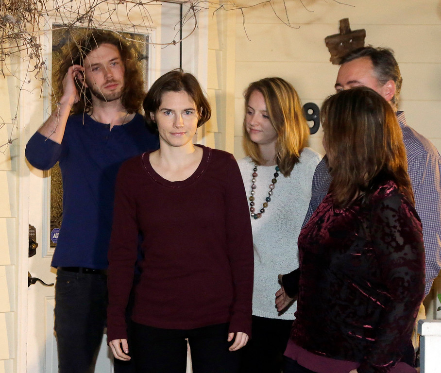 . Amanda Knox, second from left, walks with family members and her fiance, Colin Sutherland, left, as she prepares to talk to the media outside her mother\'s home, Friday, March 27, 2015, in Seattle. Italy\'s highest court overturned the murder conviction against Knox and her ex-boyfriend Friday over the 2007 slaying of Knox\'s roommate, bringing to a definitive end the high-profile case. (AP Photo/Ted S. Warren)