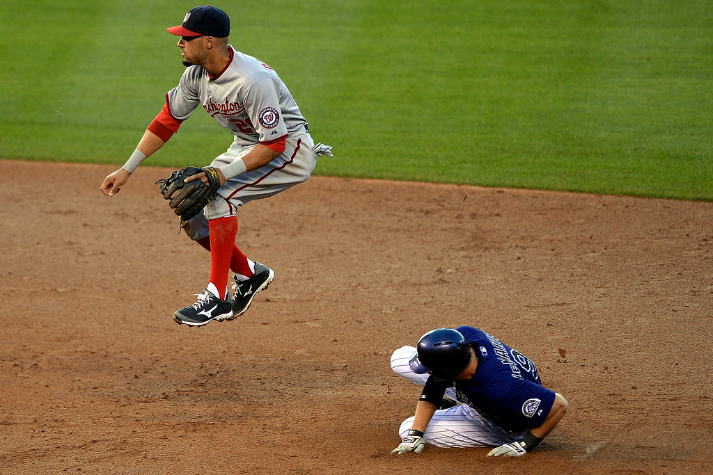 . Ian Desmond (20) of the Washington Nationals jumps to avoid contact with D.J. LeMahieu (9) of the Colorado Rockies at Coors Field. Major League Baseball action between the Colorado Rockies and the Washington Nationals on Monday, July 21, 2014. (Photo by AAron Ontiveroz/The Denver Post)