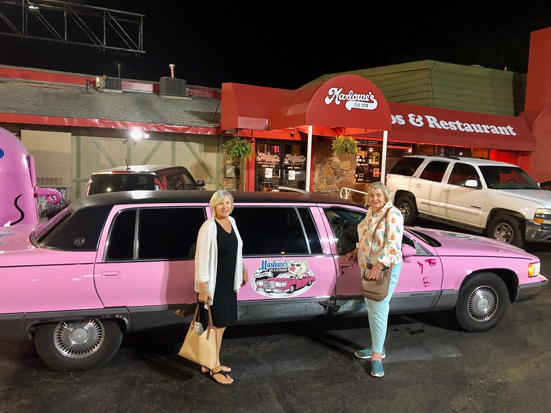 two women in front of a pink cadillac