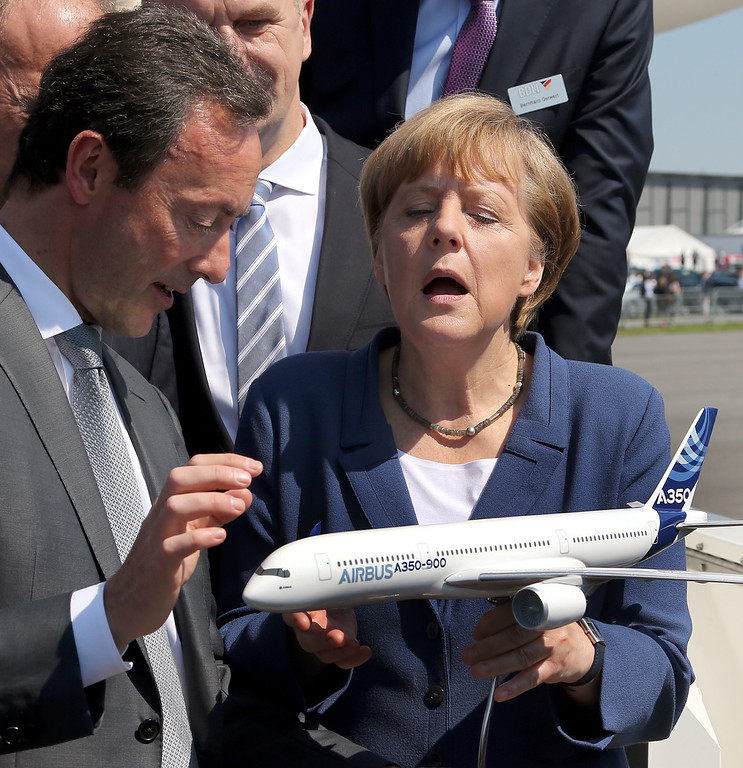 . Airbus CEO Fabrice Bregier , left,  hands over a model of an airbus 350-900 to German chancellor Angela Merkel  as she visits the  International  Air Show in Schoenefeld near Berlin, Tuesday May 20, 2014 .  (AP Photo/Wolfgang Kumm,Pool)