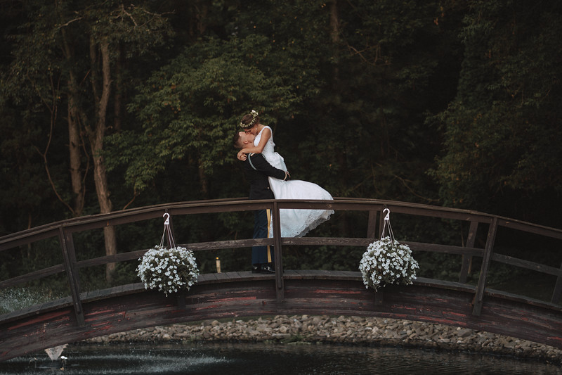 A groom lifts his bride up on a bridge as they kiss.