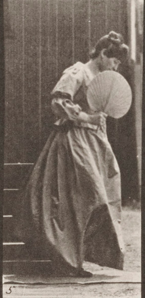 Woman with a fan in right hand descending stairs and turning having her dress caught