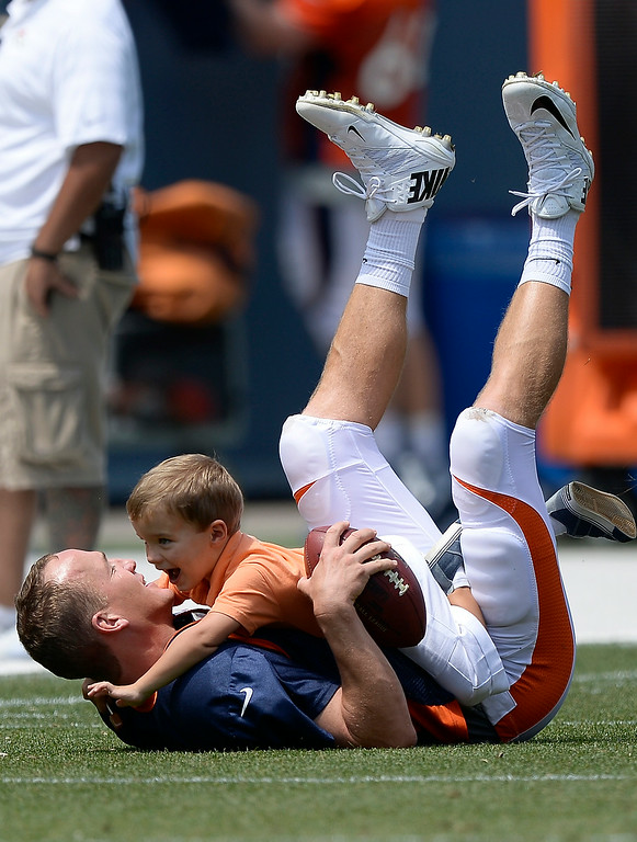 . Denver Broncos quarterback Peyton Manning (18) gets tackled by his son Marshall after practice on day four of the Denver Broncos 2014 training camp July 27, 2014 at Sports Authority Field at Mile High. The kids came out to join him on the field after he signed autographs. (Photo by John Leyba/The Denver Post)