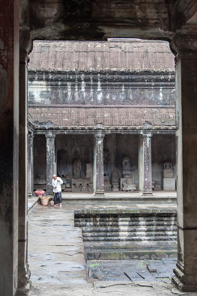 A man starts his day just after sunrise by sweeping inside Angkor Wat.