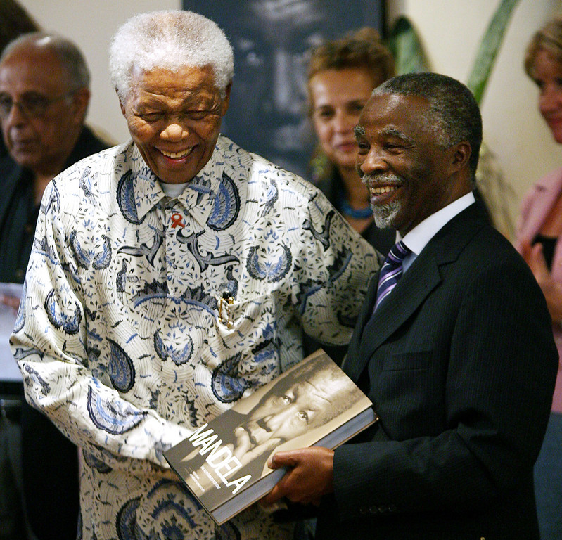 ". Former South African President Nelson Mandela gives South African President Thabo Mbeki a copy of the book ""Mandela\"" during its launch at the Mandela foundation in Johannesburg, Monday Oct. 9, 2006. (AP Photo/Jerome Delay)"