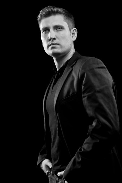 Black and white portrait of a man wearing a polo shirt and a sports jacket looking off into the distance with his hands in his pockets Alex Kaplan Photographer https://professionalheadshots.com