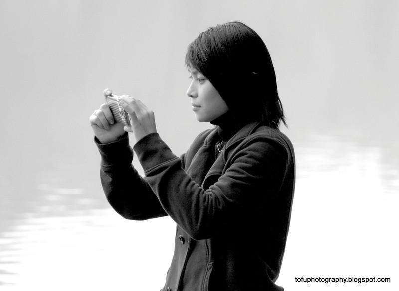 Woman taking a photo at the Hoàn Kiếm Lake in Hanoi, Vietnam in January 2012