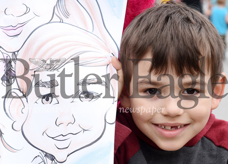 Harold Aughton/Butler Eagle: Dekland Coburn, 6, of Butler, displays a caricature of himself, Saturday afternoon, at the Butler County Recovery and Resource Block Party.