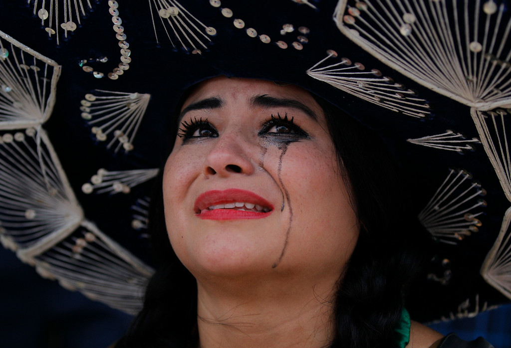 . A Mexico soccer fan cries after her team was defeat on the World Cup round of 16 match against Netherlands on a live telecast inside the FIFA Fan Fest area on Copacabana beach in Rio de Janeiro, Brazil, Sunday, June 29, 2014. The Netherlands staged a dramatic late comeback, scoring two goals in the dying minutes to beat Mexico 2-1 and advance to the World Cup quarterfinals. (AP Photo/Leo Correa)