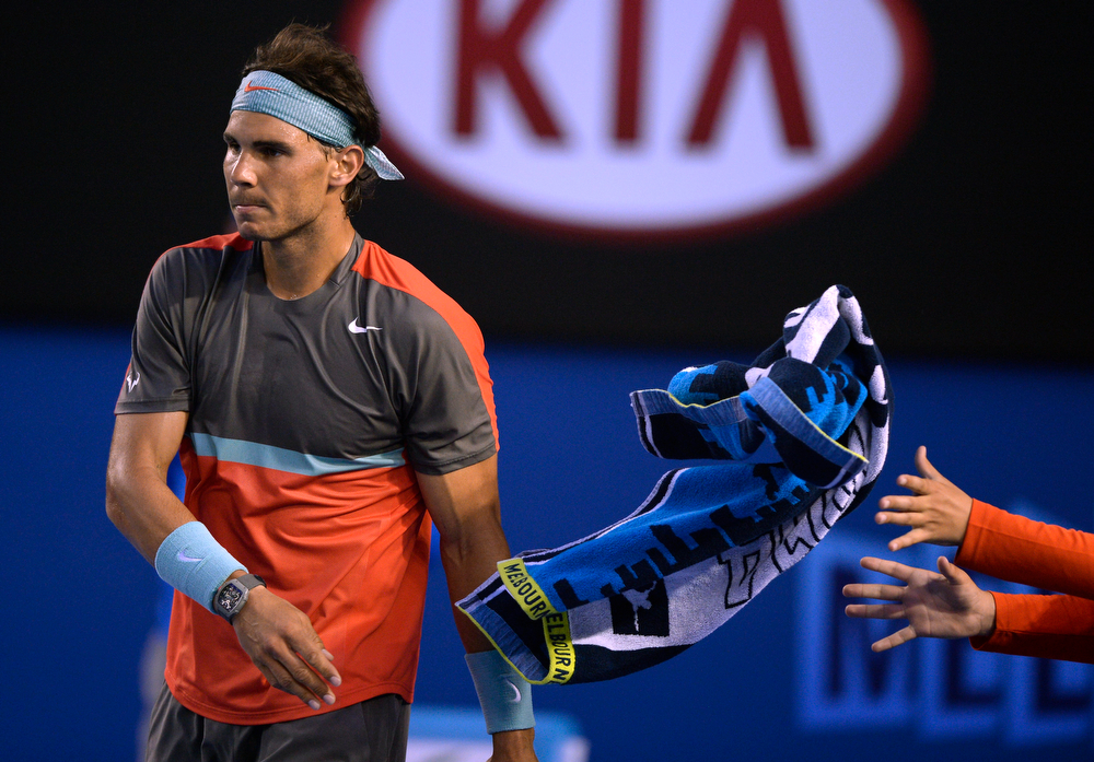 . Rafael Nadal of Spain throws a towel between points as he plays Roger Federer of Switzerland during their semifinal at the Australian Open tennis championship in Melbourne, Australia, Friday, Jan. 24, 2014.(AP Photo/Andrew Brownbill)