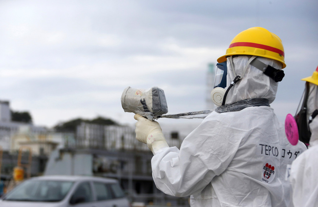. A Tokyo Electric Power Co. employee wearing a protective suit and a mask uses a radiation survey meter at the Fukushima Dai-ichi nuclear power plant in Okuma, Fukushima, northeastern Japan, Thursday, Nov. 7, 2013. The plant has recently had a series of mishaps, including leaks of radioactive water from storage tanks. The incidents, many of them caused by human error, have added to concerns about TEPCO\'s ability to safely close down the plant, which suffered multiple meltdowns after being hit by a March 2011 earthquake and tsunami. (AP Photo/Tomohiro Ohsumi, Pool)