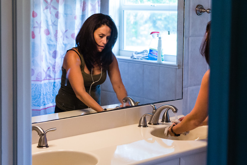"""Amy Kilgore, 37, of Philadelphia, Pennsylvania cleans the bathroom at the All About Recovery younger women's sober home in Loxahatchee, Florida on Friday, June 24, 2016. Residents are required to keep the sober home clean, but once a week, the residents  are assigned an area of the sober house to """"deep clean"""". (Joseph Forzano / The Palm Beach Post)"""