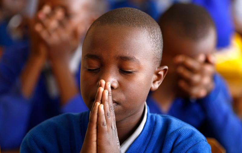 . A Kenyan pupil prays for former South African president Nelson Mandela during celebrations to mark Nelson Mandela International Day at Kilimani Primary School in Kenya\'s capital Nairobi, July 18, 2013. The ailing Mandela turns 95 today. REUTERS/Thomas Mukoya
