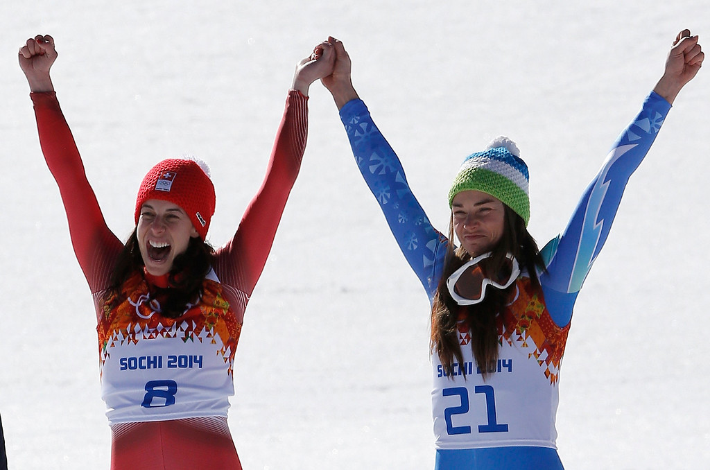 . Women\'s downhill gold medalists Switzerland\'s Dominique Gisin, left, and Slovenia\'s Tina Maze, right, hold hands during a flower ceremony at the Sochi 2014 Winter Olympics, Wednesday, Feb. 12, 2014, in Krasnaya Polyana, Russia.  (AP Photo/Christophe Ena)