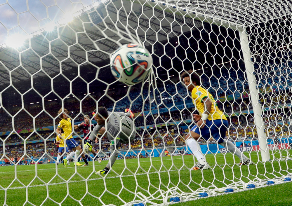 Description of . Brazil's goalkeeper Julio Cesar can not stop a shot by Germany's Thomas Mueller, background, to score his side's first goal during the World Cup semifinal soccer match between Brazil and Germany at the Mineirao Stadium in Belo Horizonte, Brazil, Tuesday, July 8, 2014. (AP Photo/Andre Penner)