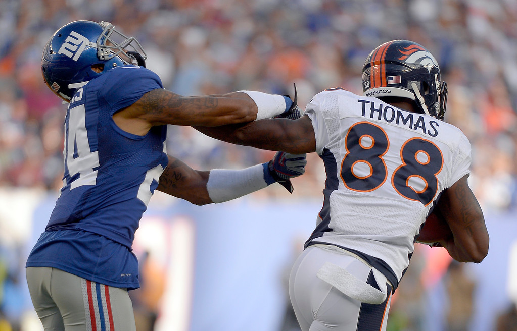 . EAST RUTHERFORD , NJ -SEPTEMBER 15: Denver Broncos wide receiver Demaryius Thomas (88) stiff arms New York Giants defensive back Terrell Thomas (24) as he picks up a few yards during the second quarter September 15, 2013 MetLife Stadium. (Photo by John Leyba/The Denver Post)