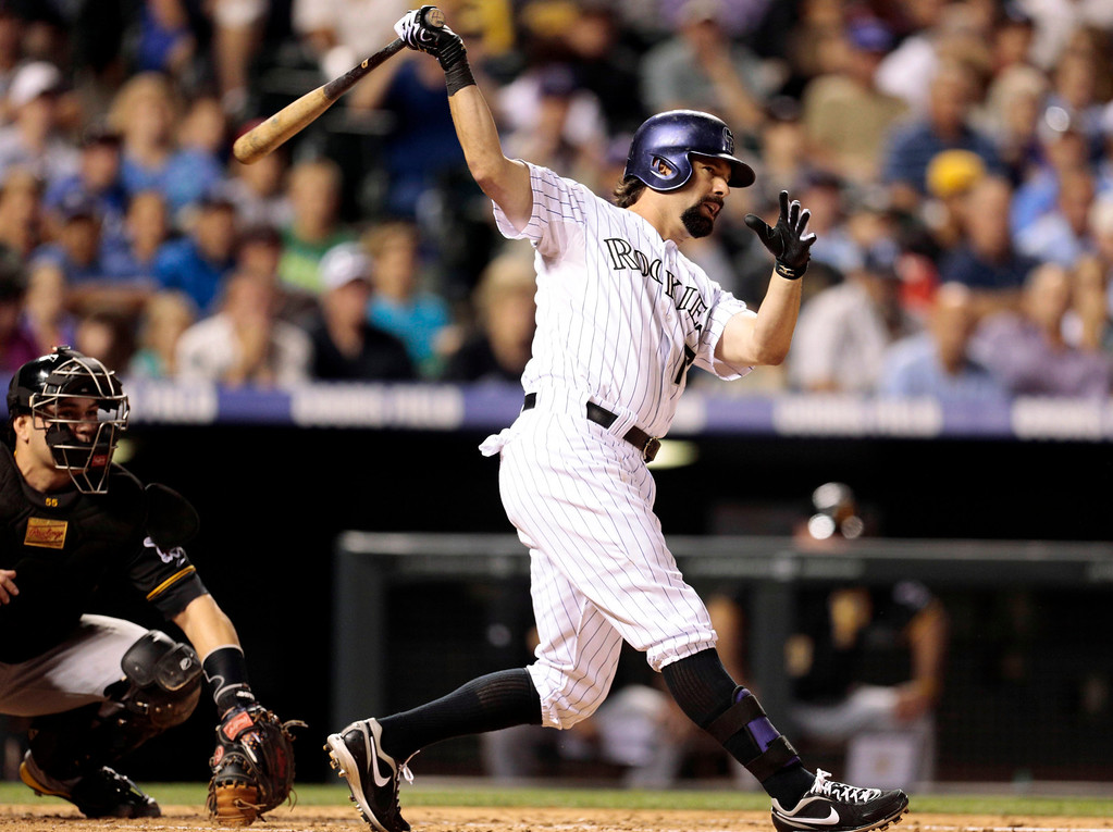 . Colorado Rockies\' Todd Helton, right, hits a double off PIttsburgh Pirates starting pitcher A.J. Burnett in the second inning of a baseball game in Denver, Saturday, Aug. 10, 2013.(AP Photo/Joe Mahoney)