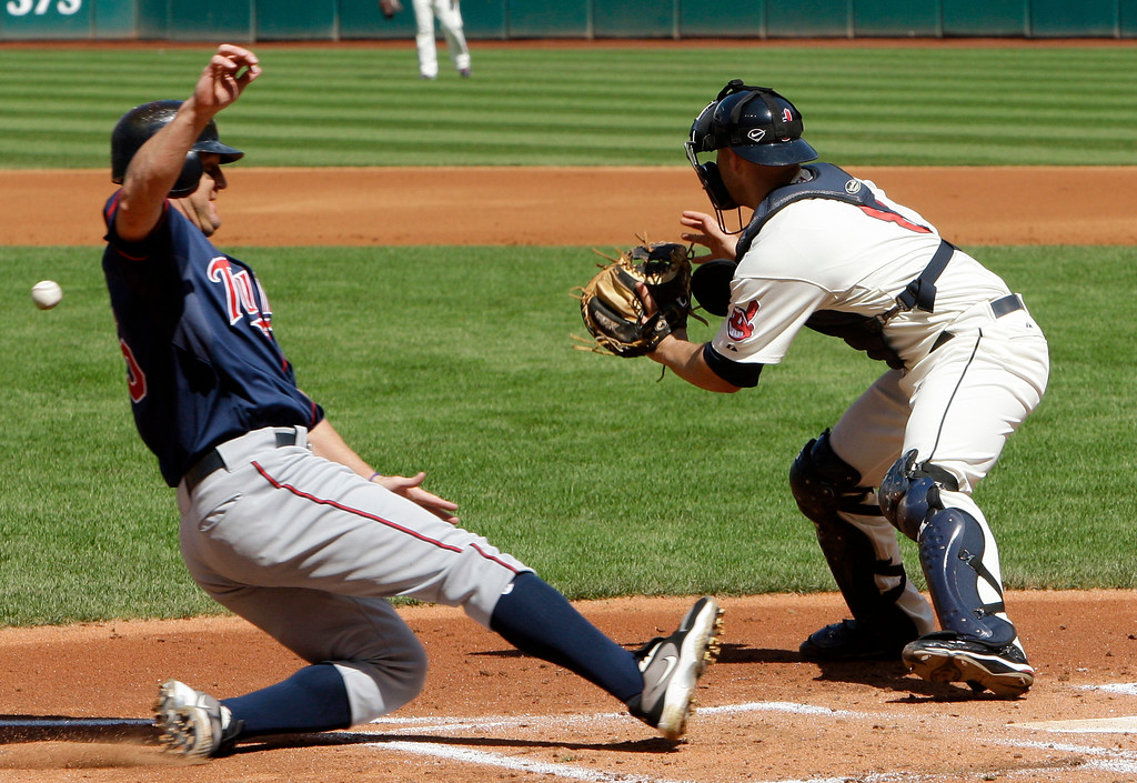 . Minnesota Twins\' Jim Thome, left, beats the throw to home as Cleveland Indians catcher Chris Gimenez waits for the ball in the first inning of a baseball game, Sunday, Sept. 12, 2010, in Cleveland. Thome scored on a single by Danny Valencia. (AP Photo/Tony Dejak)