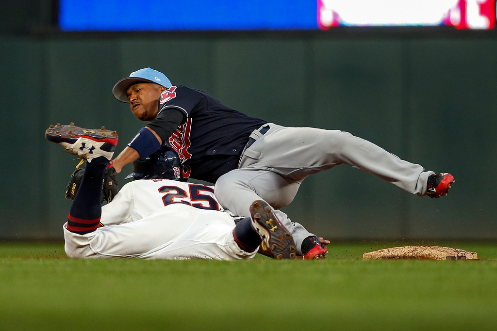 . Cleveland Indians second baseman Jose Ramirez, top, reaches for an errant throw and collides with Minnesota Twins\' Byron Buxton who advanced to third base on the play in the third inning of the second baseball game of a doubleheader Saturday, June 17, 2017, in Minneapolis. (AP Photo/Bruce Kluckhohn)